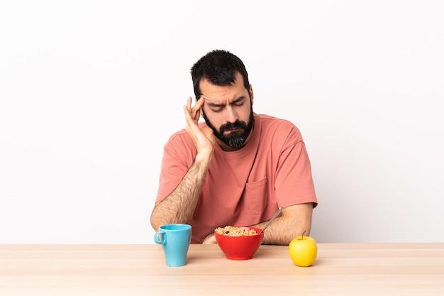 頭痛のあるテーブルで朝食をとっている白人男性。