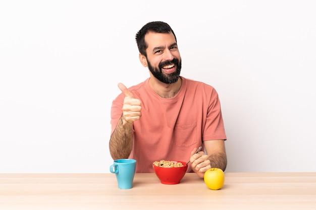 백인 남자 엄지 손가락으로 테이블에서 아침을 먹고