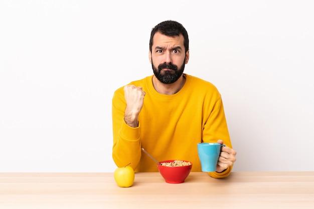 不幸な表情でテーブルで朝食を持っている白人の男