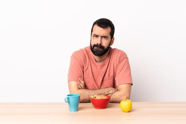 Кавказский человек завтракает в столе с несчастным выражением лица.