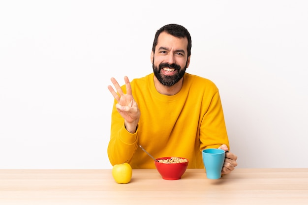 Caucasian man having breakfast in a table happy and counting three with fingers