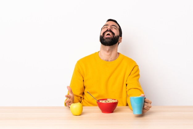 Caucasian man having breakfast in a table laughing.