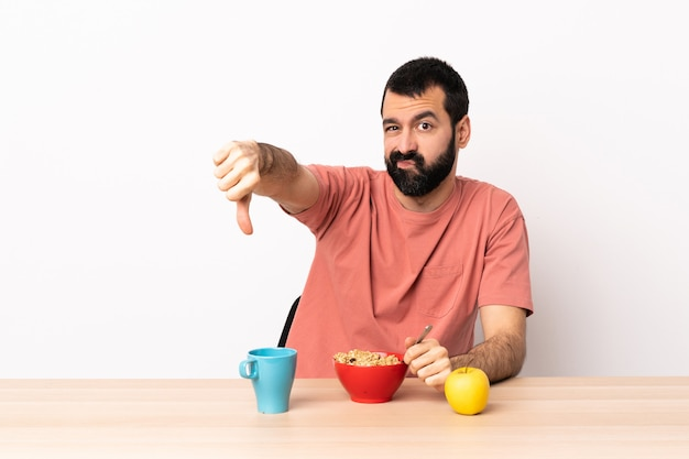 Caucasian man having breakfast in a table showing thumb down with negative expression