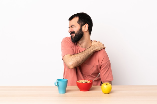 Caucasian man having breakfast in a table suffering from pain in shoulder for having made an effort