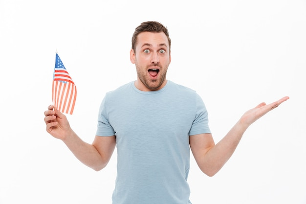 Caucasian man having bristle holding small american flag and throwing up hand in surprise