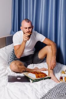 Кавказский мужчина ест фаст-фуд дома в спальне на кровати