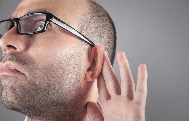 白人男性は耳の近くで手を握ります。ゴシップを聞こうとしている
