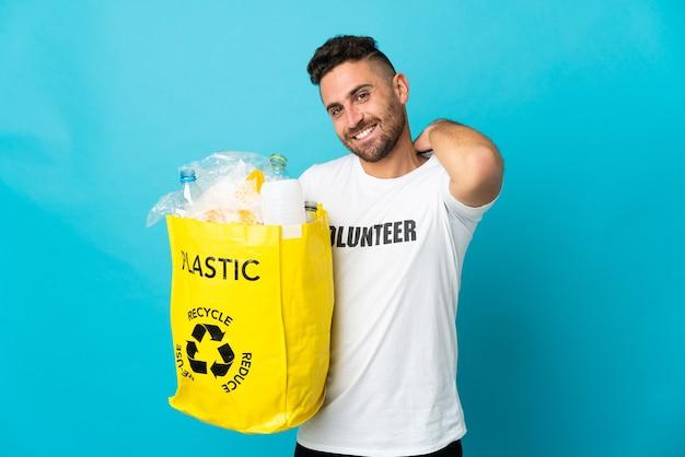 파란색 배경 웃음에 고립 재활용 플라스틱 병의 전체 가방을 들고 백인 남자