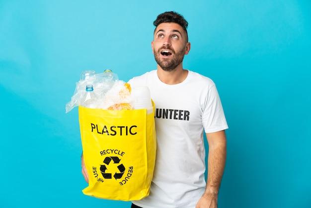 파란색 배경에 고립 된 재활용 플라스틱 병으로 가득 찬 가방을 들고 백인 남자를 찾고 놀란 표정으로