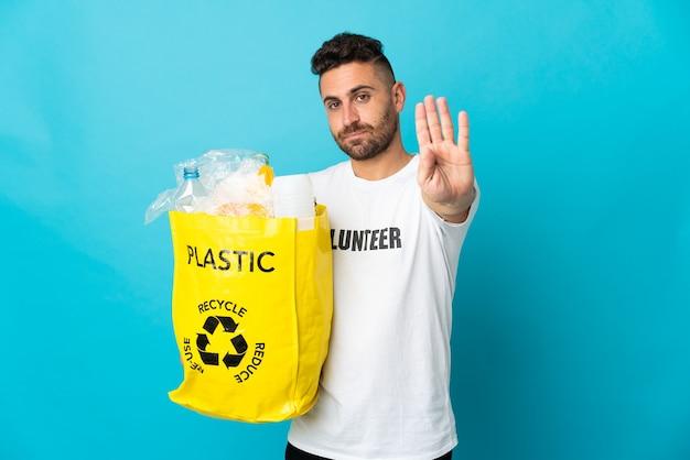 停止ジェスチャーを作る青い背景で隔離のリサイクルするためにペットボトルでいっぱいのバッグを保持している白人男性