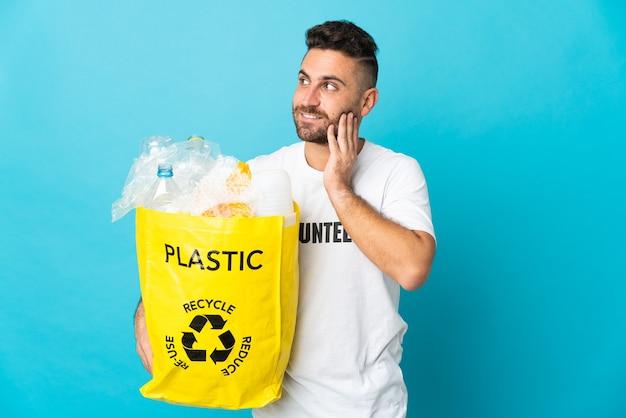 Кавказский мужчина держит сумку, полную пластиковых бутылок для переработки, изолирован на синем фоне, думая об идее, глядя вверх