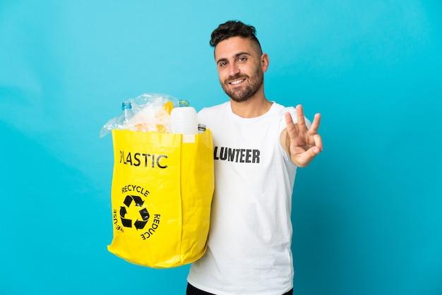 파란색 행복에 고립 된 재활용 플라스틱 병으로 가득 찬 가방을 들고 백인 남자와 손가락으로 세 세
