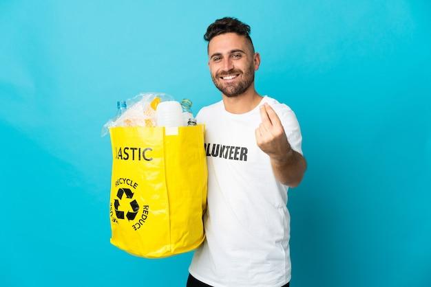 Кавказский мужчина держит мешок, полный пластиковых бутылок для переработки, изолирован на синей стене, делая денежный жест