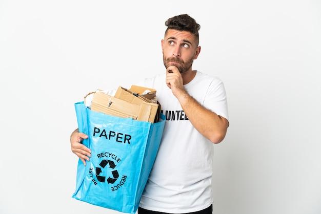 Кавказский мужчина держит мешок для рециркуляции, полный бумаги для переработки, изолированные на белом фоне, сомневаясь и думая