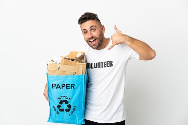Кавказский мужчина держит мешок для рециркуляции, полный бумаги для рециркуляции, изолированные на белом фоне, делая телефонный жест. перезвони мне знак