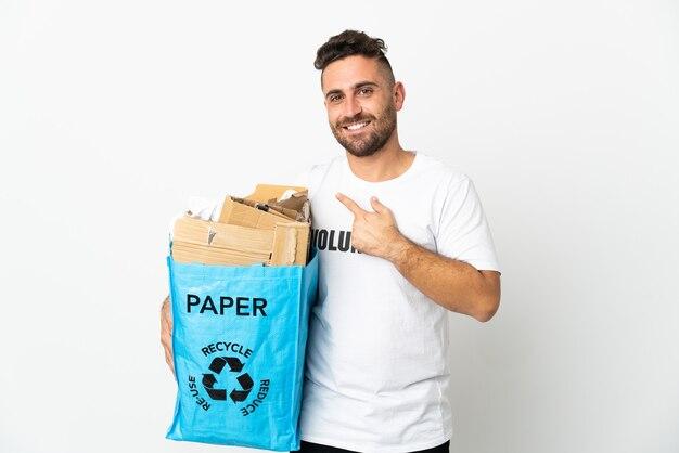 製品を提示する側を指している白い背景で隔離のリサイクルする紙でいっぱいのリサイクルバッグを保持している白人男性