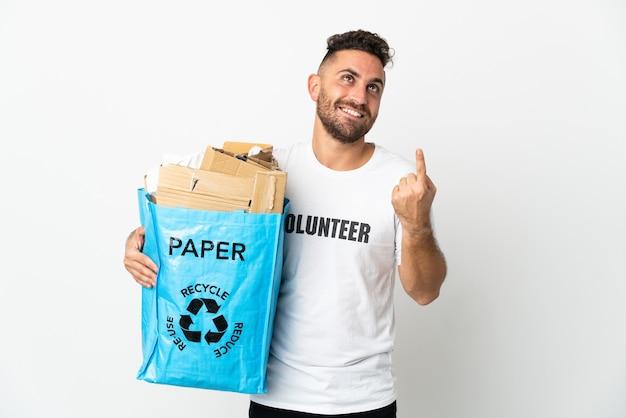 素晴らしいアイデアを指している白い背景で隔離のリサイクルする紙でいっぱいのリサイクルバッグを保持している白人男性