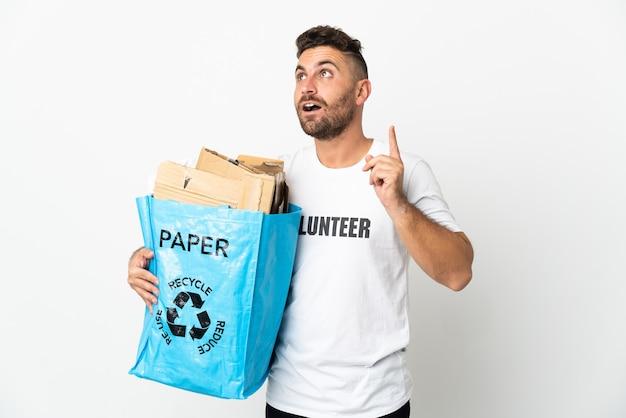 Кавказский мужчина держит мешок для рециркуляции, полный бумаги для переработки, изолирован на белом фоне, думая об идее, указывая пальцем вверх