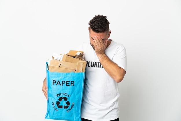 Кавказский мужчина держит мешок для рециркуляции, полный бумаги для переработки, изолирован на белом фоне с усталым и больным выражением лица