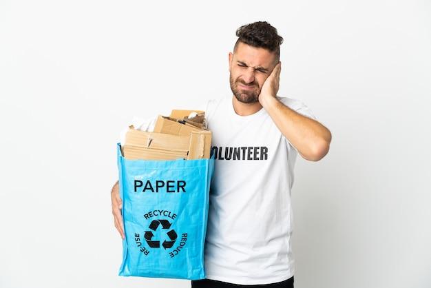 欲求不満と耳を覆っている白い壁に隔離されたリサイクルするために紙でいっぱいのリサイクルバッグを持っている白人男性