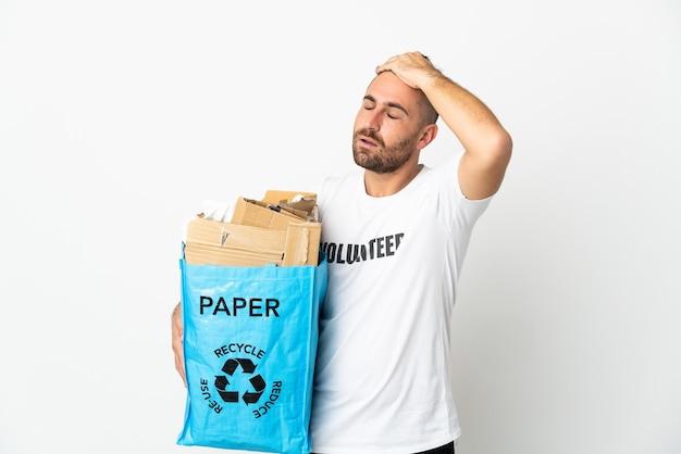 Кавказский мужчина, держащий мешок для вторичной переработки, полный бумаги для вторичной переработки, изолирован на белой стене, что-то понял и намеревается найти решение