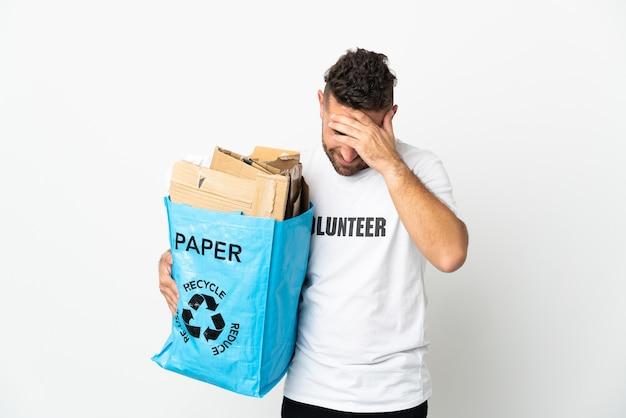 Кавказский мужчина держит мешок для рециркуляции, полный бумаги для переработки, изолирован на белой стене, смеясь