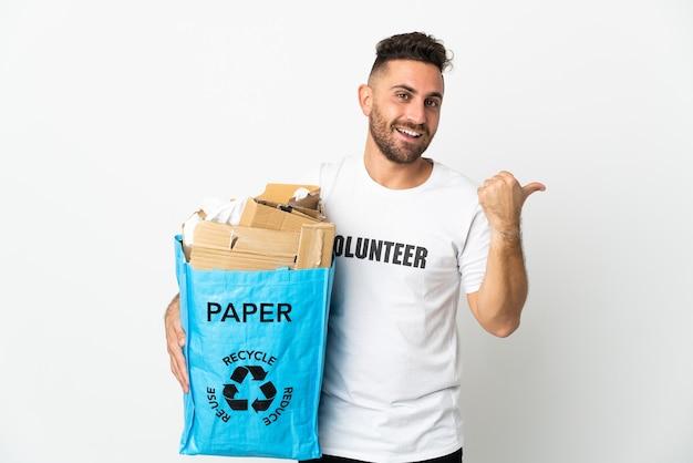 Кавказский мужчина держит мешок для рециркуляции, полный бумаги для переработки, изолирован на белой стене, указывая в сторону, чтобы представить продукт