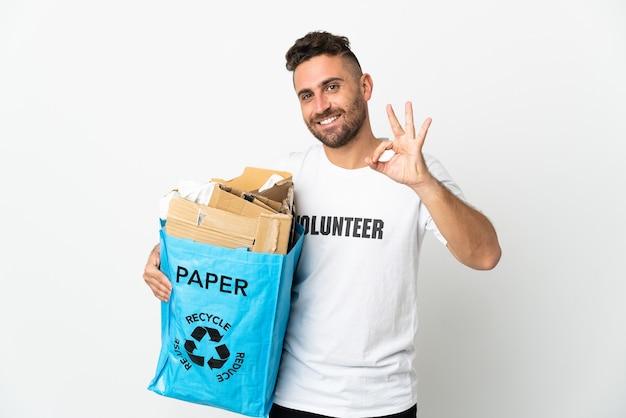 Кавказский мужчина держит мешок для рециркуляции, полный бумаги для переработки, изолирован на белой стене, показывая пальцами знак ок