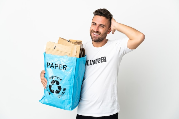 Кавказский мужчина держит мешок для рециркуляции, полный бумаги для рециркуляции, изолирован на белой стене, много улыбаясь