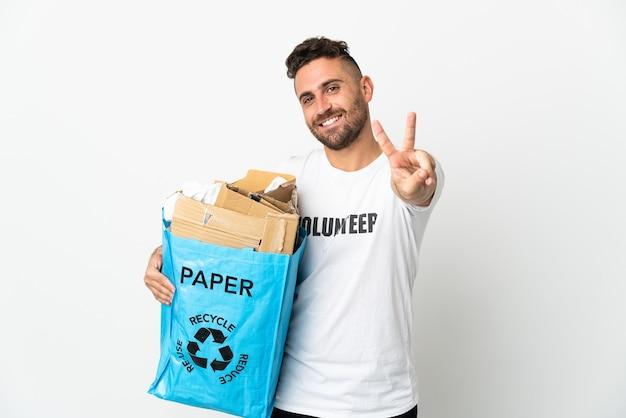 Кавказский мужчина держит мешок для рециркуляции, полный бумаги для переработки, изолирован на белой стене, улыбается и показывает знак победы