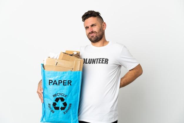 Кавказский мужчина держит мешок для переработки, полный бумаги для переработки, изолирован на белой стене, страдает от боли в спине из-за того, что приложил усилие