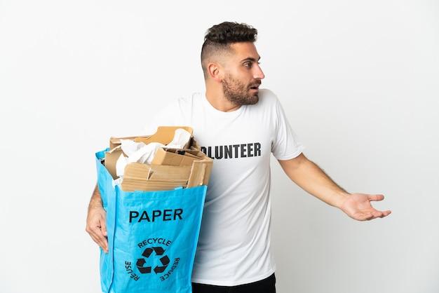 Кавказский мужчина держит мешок для переработки, полный бумаги для переработки, изолирован на белой стене с удивленным выражением лица, глядя в сторону