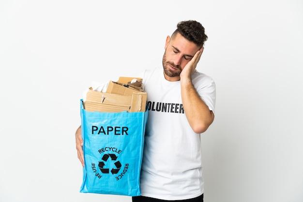 Кавказский мужчина держит мешок для рециркуляции, полный бумаги для переработки, изолированные