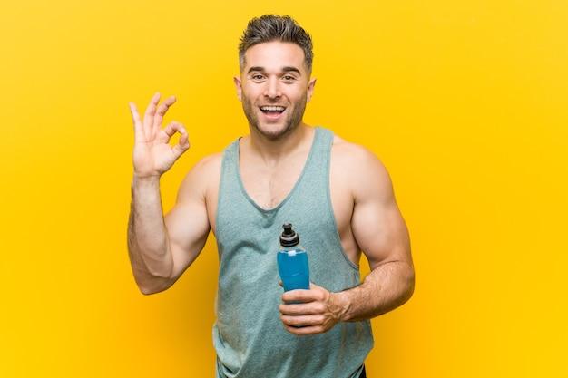 エネルギードリンクを持っている白人男性は、陽気で自信を持って大丈夫なジェスチャーを示しています。