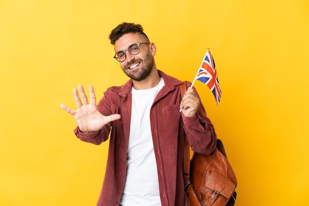 指で5を数える黄色の背景に分離されたイギリスの旗を保持している白人男性