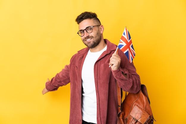 黄色の背景に分離されたイギリスの旗を持っている白人男性は、来て招待するために手を横に伸ばします