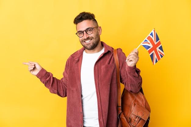 측면에 손가락을 가리키는 노란색 배경에 고립 된 영국 국기를 들고 백인 남자