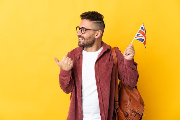 제품을 제시하기 위해 측면을 가리키는 노란색 배경에 고립 된 영국 국기를 들고 백인 남자