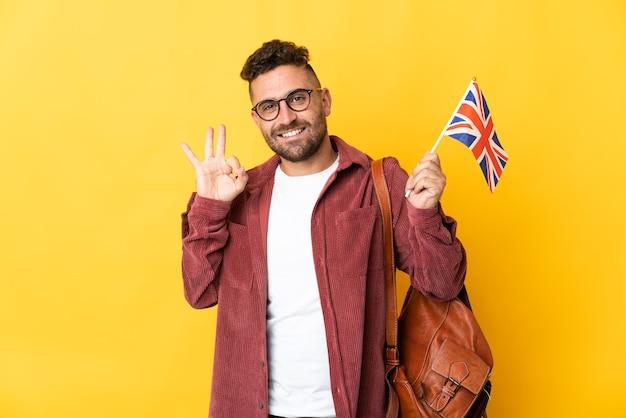指でokサインを示す黄色の背景に分離されたイギリスの旗を保持している白人男性