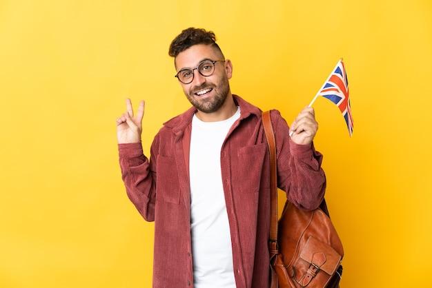 웃 고 승리 기호를 보여주는 노란색 배경에 고립 된 영국 국기를 들고 백인 남자