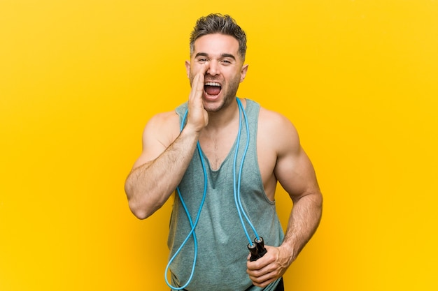 Caucasian man holding a jump rope shouting excited to front.