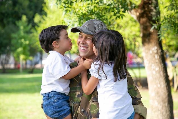 Uomo caucasico che tiene i bambini e sorride. bambini svegli felici che abbracciano e baciano il padre di mezza età in uniforme militare. papà che torna dall'esercito. ricongiungimento familiare, paternità e concetto di ritorno a casa