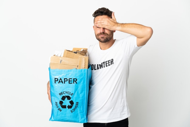 Caucasian man holding a recycling bag full of paper to recycle isolated on white background covering eyes by hands. do not want to see something