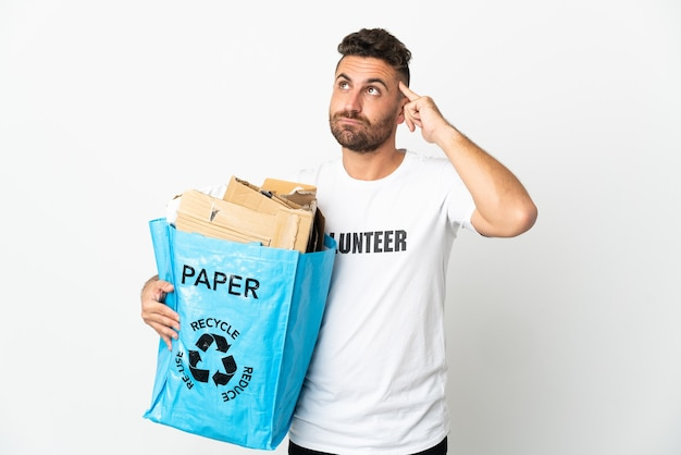 Caucasian man holding a recycling bag full of paper to recycle isolated on white background having doubts and thinking