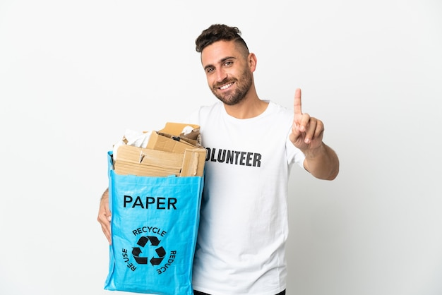 Caucasian man holding a recycling bag full of paper to recycle isolated on white background showing and lifting a finger