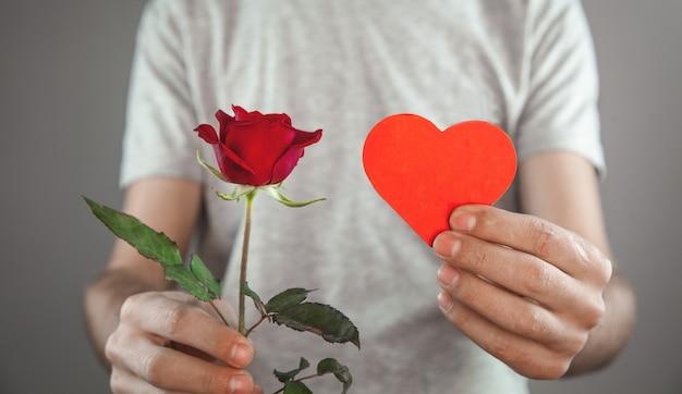 赤いハートと赤いバラの花を保持している白人男性。
