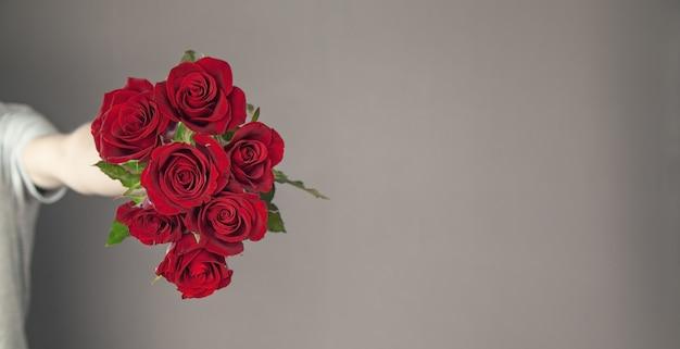 赤いバラの花を持っている白人男性。