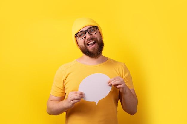 노란색 배경 위에 텍스트를 위한 빈 공간이 있는 말풍선을 들고 있는 백인 남자