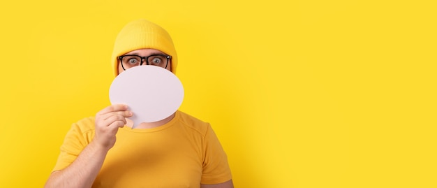 Caucasian man holding speech bubble with empty space for text over yellow background, panoramic layout