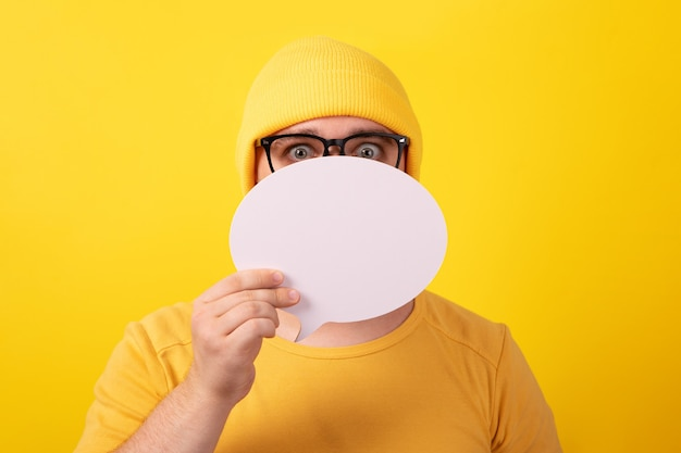 Caucasian man holding speech bubble with empty space for text over yellow background